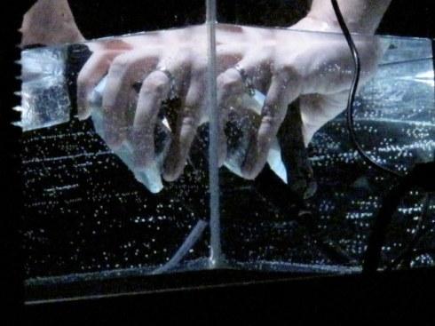 les mains de l'artiste manipulent un micro dans l'eau
